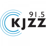 Logo for KJZZ 91.5 radio station: black font against a white background, with a series of concentric semi-circles on the left side, in blue.